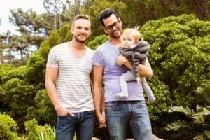 Casal homoafetivo sorrindo enquanto um deles segura o pequeno filho no colo