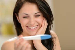 Jovem mulher sorrindo e feliz após confirmar que está grávida, com teste de gravidez nas mãos