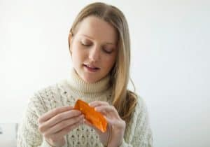 Jovem adolescente loira de malha bege, no quarto, abre uma cartela de remédio