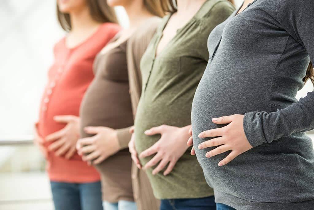 Diversas grávidas enfileiradas, cada uma de uma idade