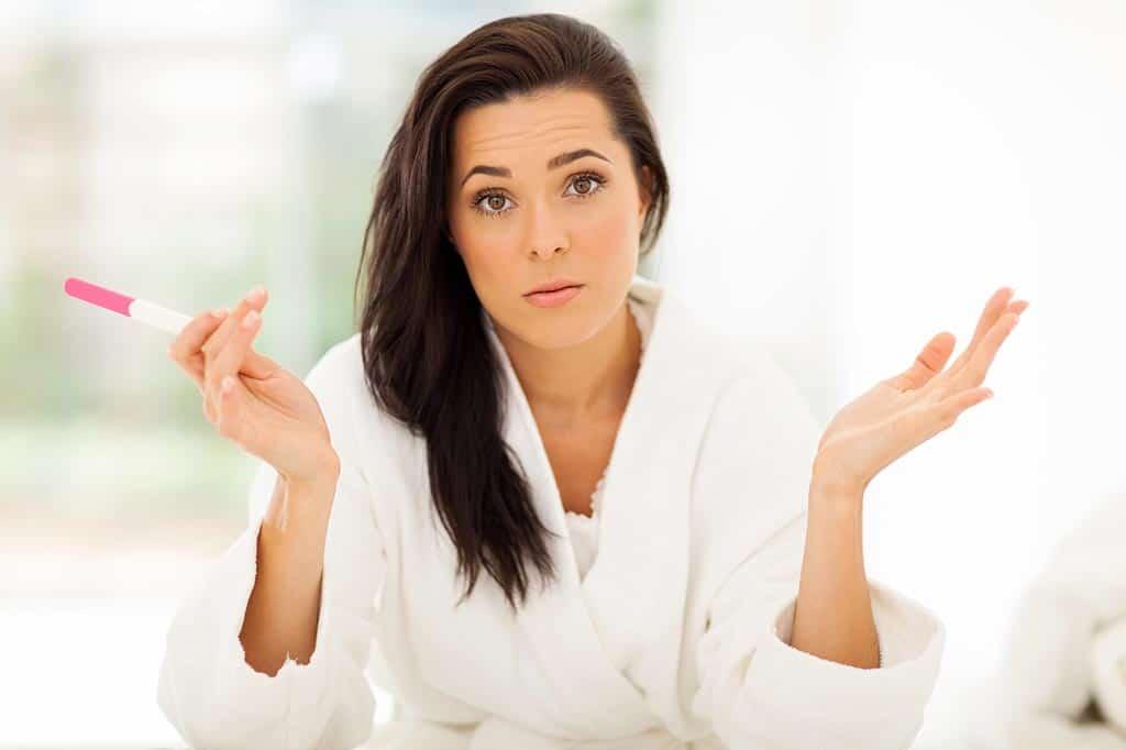 Mulher com expressão de dúvida e frustração por infertilidade feminina segura teste de gravidez negativo na mão