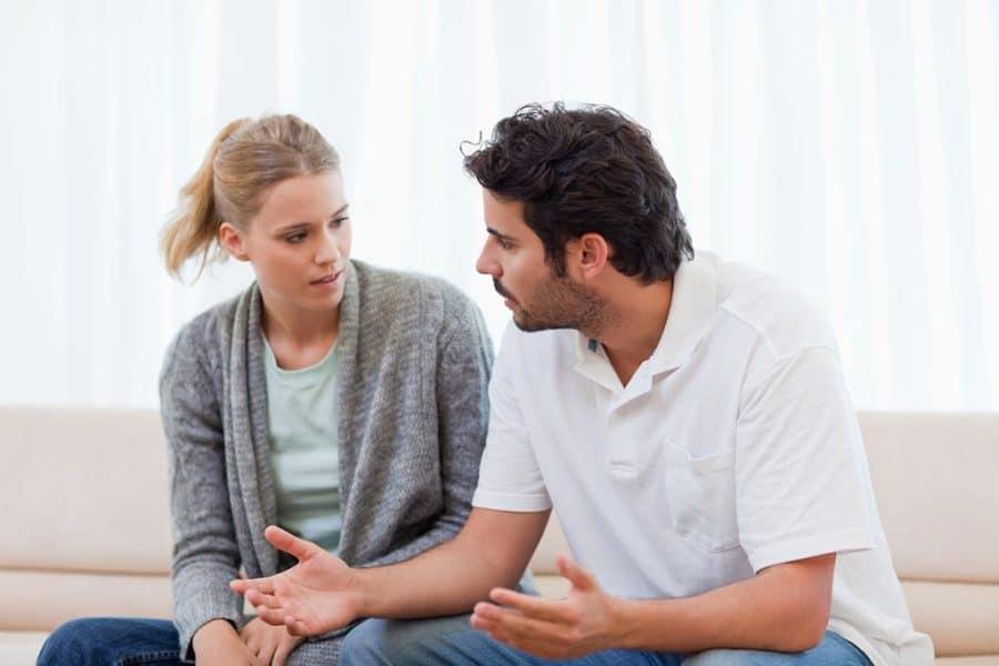 Casal sentado na sala com expressão tensa conversam sobre infertilidade masculina