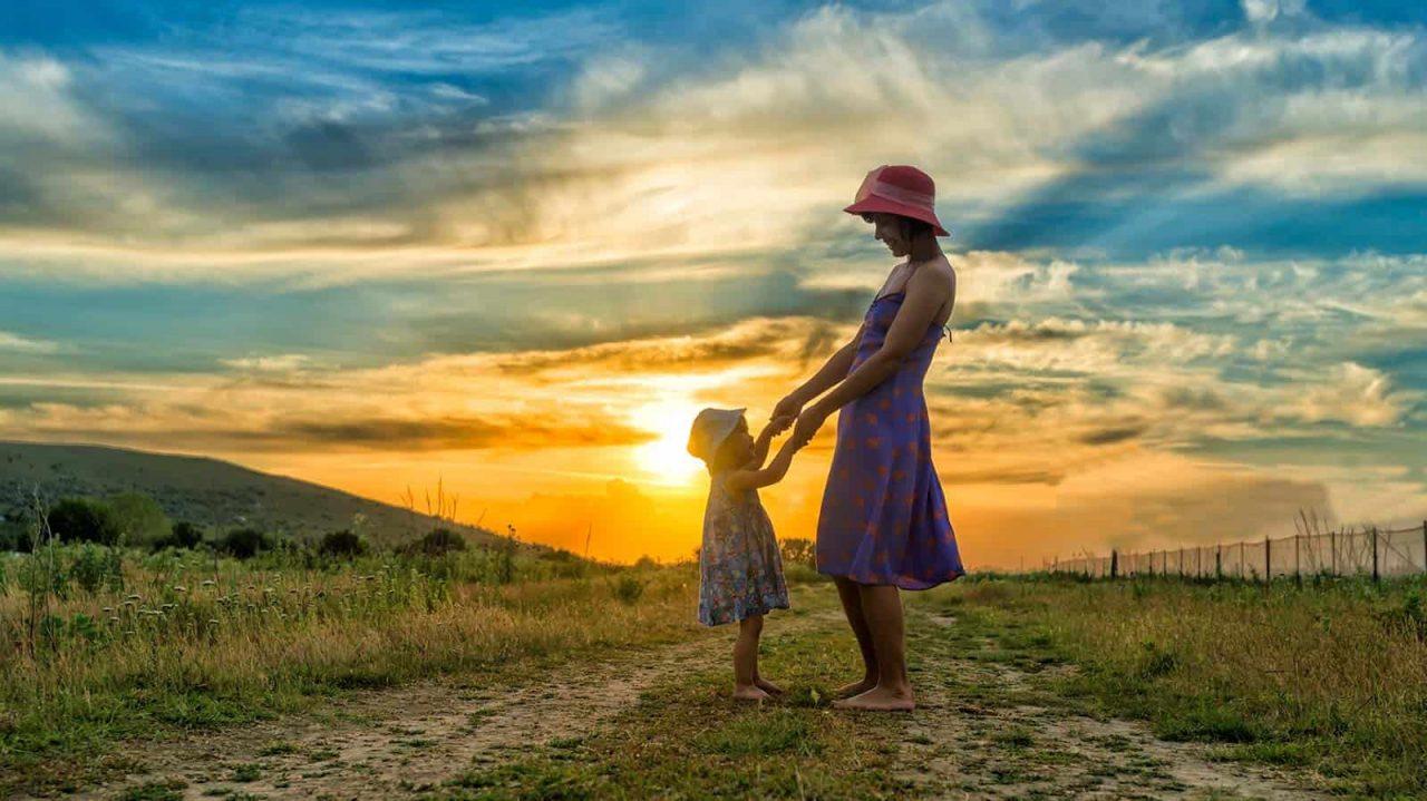 Mãe de chapéu de mãos dadas com a pequena filha num caminho de terra na natureza com por do sol ao fundo