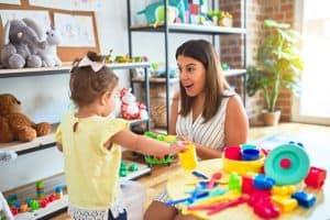 Jovem mãe brinca com sua filha em casa
