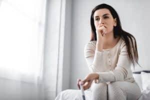 Mulher com ar de dúvida segura um teste de gravidez negativo sentada na cama do quarto